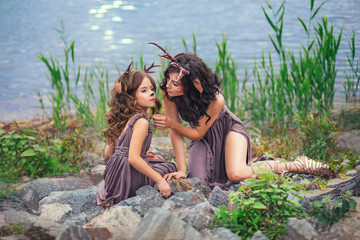 family photo of mother and child, fauns on the shore of a large lake are sitting on stones, fairy-tale characters, the mother reaches out for her daughter, while the baby looks around with interest