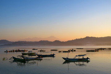 Black fishermans boats silhouettes in the morning at Lombok island, Indonesia