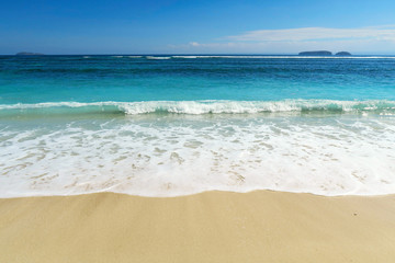 Ideal white clear sand ocean beach with small waves and foam