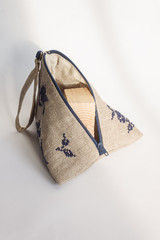 Linen cosmetic bag with a blue embroidery. Light background