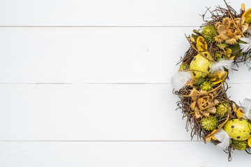 Easter wreath with flowers on white wooden background