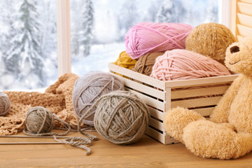 Woolen yarn and fabric on the window sill. Beautiful view outside the window - winter scenery and snow.