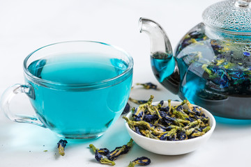 Butterfly pea flower blue tea in a cup with teapot on white marble table. Healthy detox herbal drink