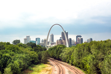"""St. Louis, the """"Gateway to the West."""" Skyline seen over trees with train tracks leading into the city"""