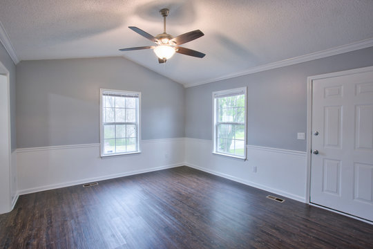 Gray living room interior with vaulted ceilings and chair rail.