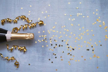 Champagne bottle with confetti stars and party streamers on blue background. Copy space,top view. Flat lay