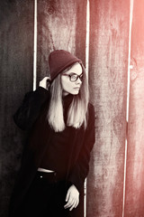 Stylish hipster model in glasses and hat holding hair. Toned picture of lonely teenager on a cold autumn day