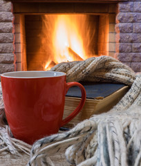 Cozy scene before fireplace with red mug of tea, a book, wool scarf.