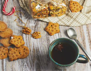 clay Cup of black tea with a handful of cookies on a white, old, shabby wooden table, vertical view. the composition of the morning Breakfast in a rustic style with cookies.