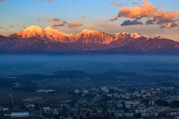 Kamnik-Savinja Alps rising above the city of Kranj at the sunset