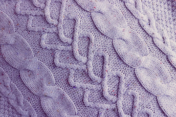Beautiful texture of a soft warm natural sweater with a knitted pattern of threads. The background
