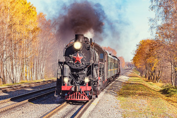 Steam train moves toward at autumn day time.