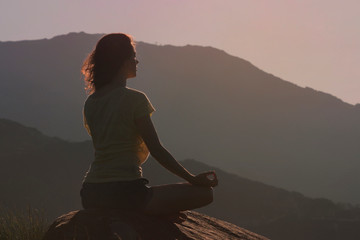 Woman sitting on the rock and meditating in yoga pose. Back view