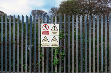 Hazard warning signs on fence around industrial plant handling dangerous toxic chemical agents, including chlorine.
