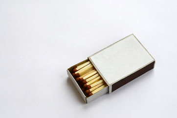 Open cardboard matchbox filled with matches on a white background