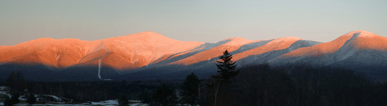 panoramic scenery of snow mountains with red sunlight on peak