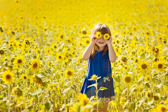 happy little girl with fun playing among the blooming sunflowers, closing her eyes with flowers