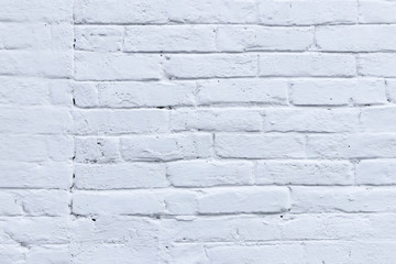 The texture of the wall of the old bricks covered with white paint. White brick wall and masonry. Grunge background and wallpaper with space for text or image. Empty template and mockup for designers.