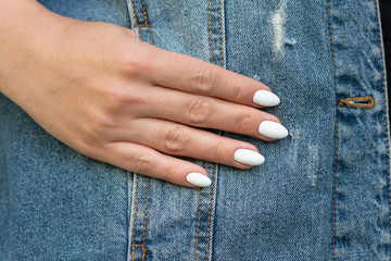girl's hand in the pocket of a denim jacket
