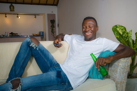attractive and happy black afro American man relaxed at home sofa couch enjoying watching television sports or movie smiling cheerful holding TV remote controller