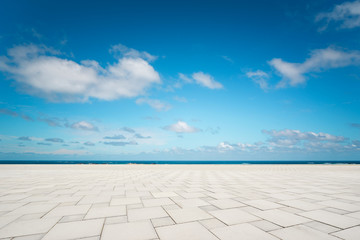 Outdoor empty square marble floor and sea under the blue sky . Wall mural