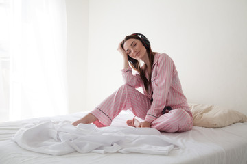 beautiful woman in pink Pajamas listening to music with headphones on the bed