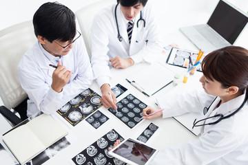 レントゲン写真を見ながら今後の治療計画を練る医師
