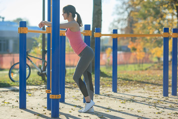 Tired young athletic girl is standing beside a sports simulator on a street playground in the autumn.