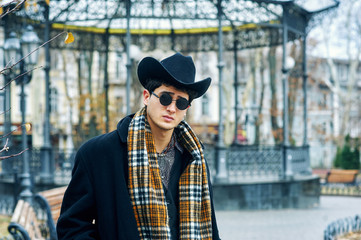 Portrait of a young man in the city . The man is dressed in a dark coat and a wide-brimmed hat