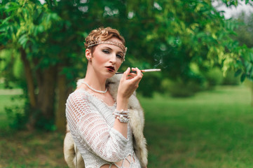 Colorful photography of young smoking woman wearing knitted long white dress.  Outdoors image