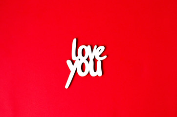 The wooden word love you on a red background.