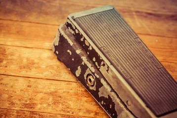 Old Beaten Up Guitar Wah Wah Pedal on a Dirty Hard Wood Floor.