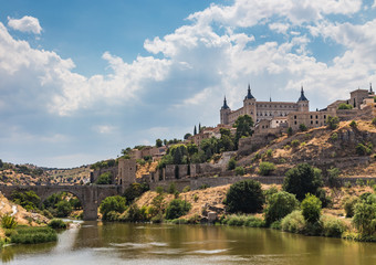 View of the old city and the Alcantara Bridge leading to the Gate of the Sun from the side of the River Tajo Toledo, Spain.