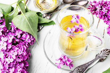 Fototapete - Cup of tea and lilac flowers