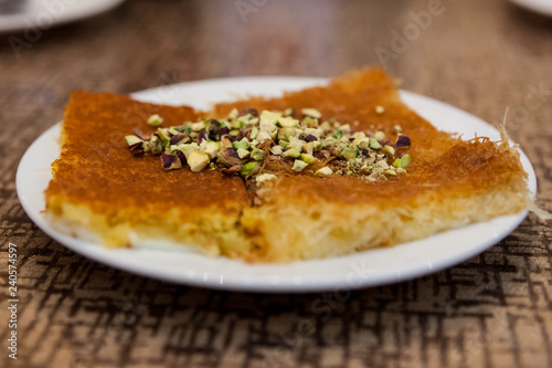 A plate of kunafah, a popular Arabian dessert, topped with chopped