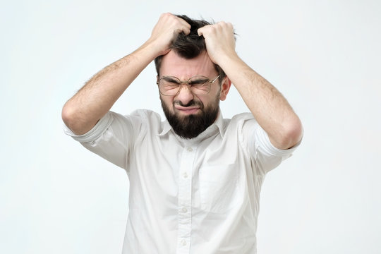 Enraged young businessman pulling his hair out for exasperation, having a burnout at work, screaming for frustration and stress