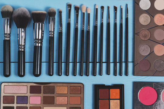 topview of set of different make up cosmetics and brushes on wooden blue background. Texture. flat lay.