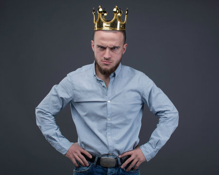 Aggressive man in the gold crown with arms akimbo is staying and watchig into the camera