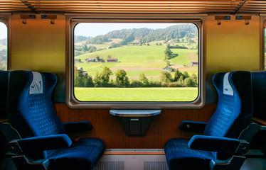 Swiss rural farmland through train window, Train travel concept.