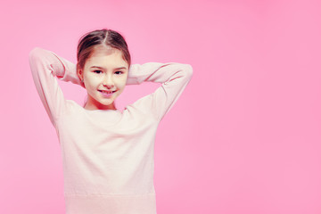 Cute child girl with hands behind head in a relaxed pose over pink background