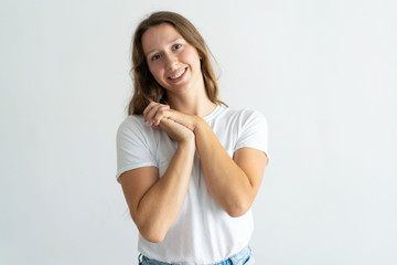 Smiling lovely young woman with her hands clasped. Lady looking at camera. Gratitude concept. Isolated front view on white background.