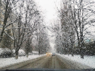 Car window with drops of water on it and blurred road with cars and winter trees with snow on branches. Empty slippery road with selective focus and car lights with linen perspective and foggy scene