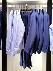 Man elegance classic formal cloth on wooden hangers. Design blue mens fashion jackets, trouses and shirts. Menswear sale. Man wardrobe for official dress code. Casual ironed clothes on metal rack
