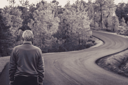Active senior man stands alone on lonely road between mountains in black and white