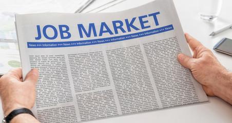 Man reading newspaper with the headline Job Market