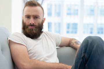 Pensive bearded guy posing at home. Young man in casual sitting on couch and staring at camera. Leisure at home concept