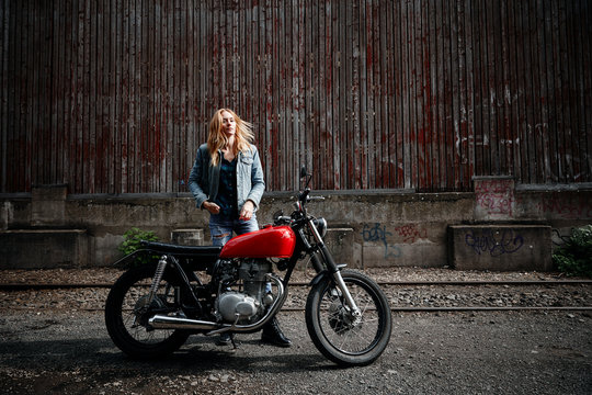Young woman with motorcycle standing outdoors