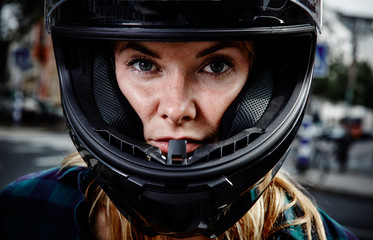 Portrait of confident young woman wearing motorcycle helmet
