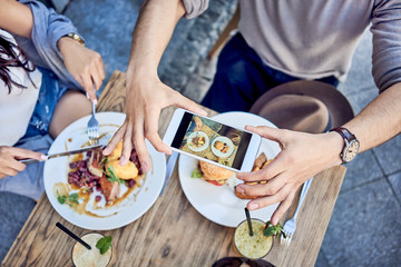 Overhead view of couple taking photo of food at outdoors restaurant