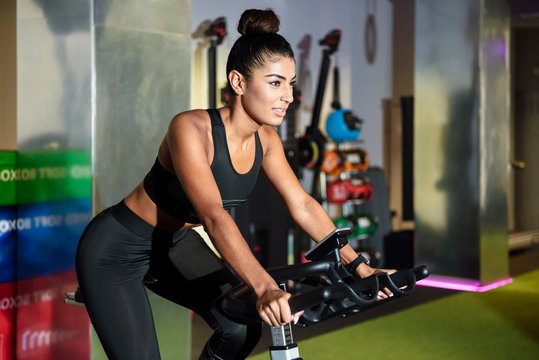 Woman on spinning bike in a gym